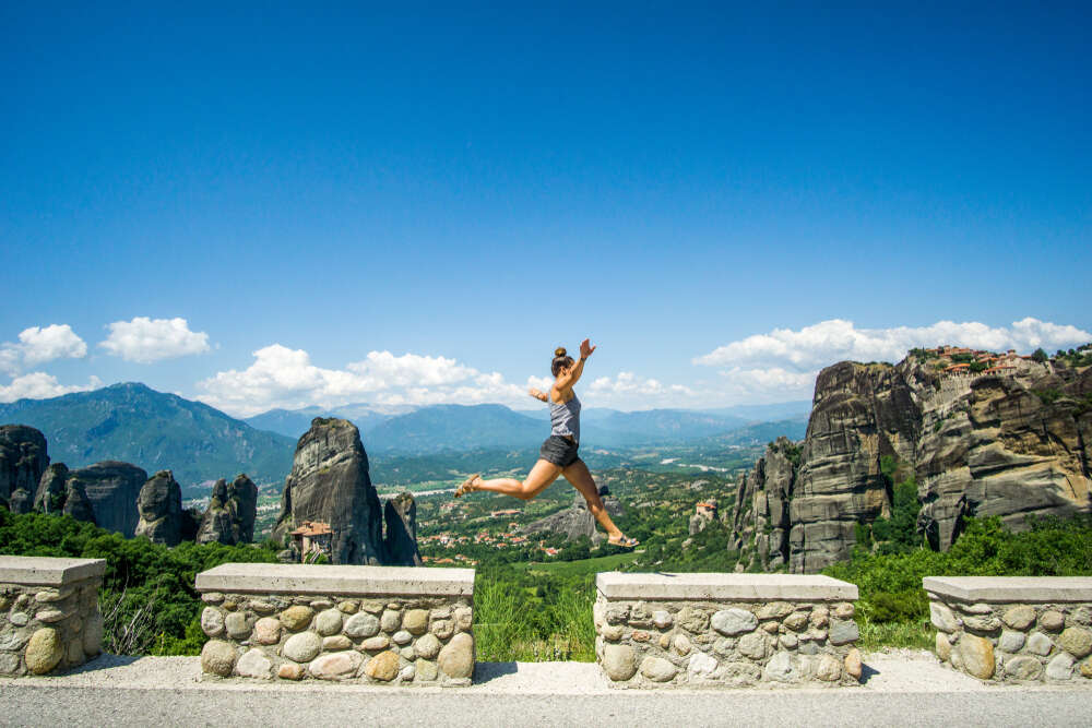 A girl jumping in front of mountainous